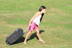 Girl with heavy suitcase. Little barefoot girl in pink shorts and white t-shirt carrying heavy black chech-in baggage Royalty Free Stock Image