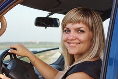 Girl after the helm of car. Young beautiful girl after the helm of car Royalty Free Stock Images