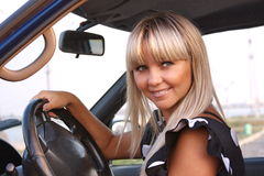 Girl after the helm of car Stock Image