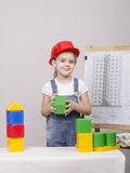 The girl in helmet builds a house on drawing Stock Photo
