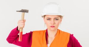Girl in helmet or hard hat raise up hammer. Young strong woman works as builder. Feminism concept. Woman with strict face holds hammer, isolated on white Stock Image