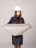 Girl in helmet looks a project expanding hands drawing Royalty Free Stock Photo