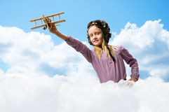 Girl in helmet pilot playing with a toy airplane Stock Photo
