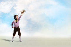 Girl in helmet pilot playing with a toy airplane Royalty Free Stock Image