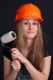 Girl in a helmet with a roller in his hand. Girl in a helmet with a roller to paint in his hand Royalty Free Stock Photos