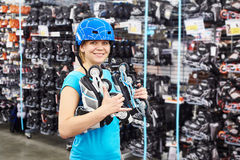 Girl in helmet and with rollers in sports shop Royalty Free Stock Image