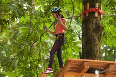 Child in a adventure playground. A girl in a helmet and safety equipment in adventure ropes park on the background of nature Stock Image