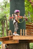 Child in a adventure playground. A girl in a helmet and safety equipment in adventure ropes park on the background of nature Stock Photography