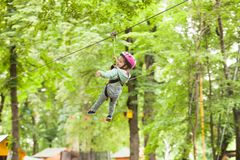 Child in a adventure playground. Girl in a helmet and safety equipment in adventure ropes park get down in the end of way Stock Photos