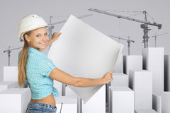 Girl in helmet showing empty paper sheet. White Royalty Free Stock Photo