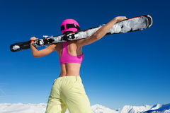 Girl in helmet with skis against of snowy mountain Stock Photos