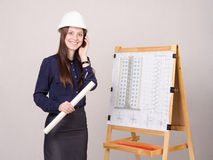Girl a helmet talking on phone with drawing in hands Royalty Free Stock Photos