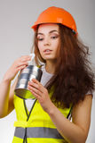 Girl in a helmet and vest looks into the open metal container. Stock Image