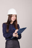 Girl a helmet writes in pencil folder Royalty Free Stock Photography