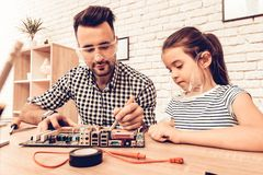 Girl Help Father Repair Device on Table at Home. royalty free stock photography