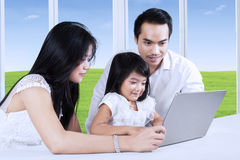 Girl helped by her parents to study Stock Images