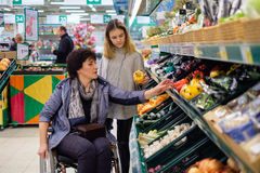 Girl helping disabled mothter in a grocery store. Young girl helping her disabled mothter in wheelchair in a grocery store Royalty Free Stock Photography