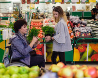 Girl helping disabled mothter in a grocery store. Young girl helping her disabled mothter in wheelchair in a grocery store Stock Photos