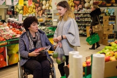 Girl helping disabled mothter in a grocery store. Young girl helping her disabled mothter in wheelchair in a grocery store Royalty Free Stock Photo
