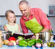 Girl helping father to prepare dinner Stock Photography