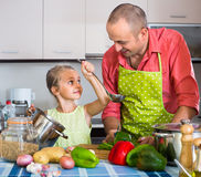 Girl helping father to prepare dinner Stock Photo