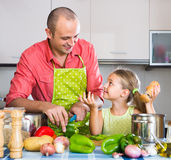 Girl helping father to prepare dinner Royalty Free Stock Photos