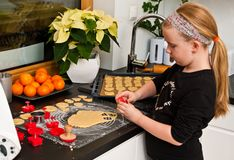 Girl helping with ginger Christmas cooking Royalty Free Stock Images