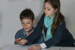 Girl helping her brother. Concentrated teenager boy sitting at his desk  doing his maths school  homework. He gets help from his sister Stock Photography