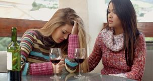 Girl Helping her Depressed Friend at the Cafe. Kind Girl Helping her Friend Suffering from Depression While Drinking Wine at the Cafe stock footage