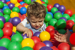 Girl helping her little brother getting out a ball pool Stock Image