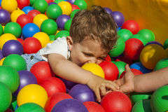 Girl helping her little brother getting out a ball pool Royalty Free Stock Images
