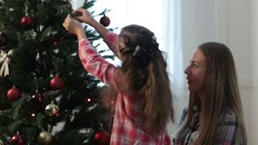 Girl helping her mom to decorate family xmas tree stock video footage