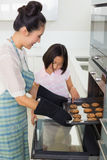 Girl helping her mother prepare cookies in kitchen Royalty Free Stock Image