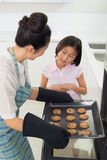 Girl helping her mother prepare cookies in kitchen. Young girl helping her mother prepare cookies in the kitchen at home stock photography