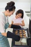 Girl helping her mother prepare cookies in kitchen Stock Photos