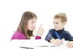 Girl helping her naughty brother with his homework. Teenage girl helping her naughty brother with his homework. Pointing at him Royalty Free Stock Image