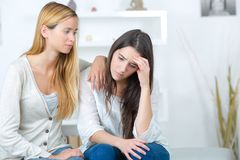 Girl helping sad sister with problems Stock Photo