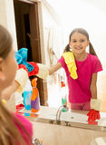 Girl helping at housework and cleaning bathroom mirror Stock Photo
