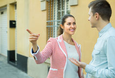 Girl helping lost male tourist. Cheerful young brunette helping lost male tourist to find way Royalty Free Stock Image