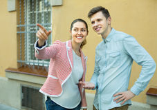 Girl helping lost male tourist. Friendly brunette girl helping lost male tourist to find the right direction Stock Image