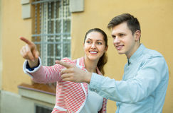 Girl helping lost male tourist. Friendly smiling young brunette helping lost male tourist to find way . Focus on man Royalty Free Stock Photography