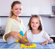Girl helping mom dusting Royalty Free Stock Photography