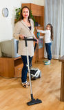 Girl helping mom to clean furniture Stock Photo