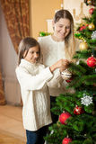 Girl helping mother to decorate Christmas tree at living room Stock Image