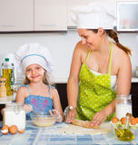 Girl helping mother to make a dough. Cheerful smiling cute little girl helping mother to make a dough Royalty Free Stock Photo