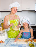 Girl helping mother to make a dough Stock Images