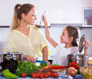 Girl helping mother to prepare Royalty Free Stock Photos
