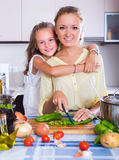 Girl helping mother to prepare Royalty Free Stock Images