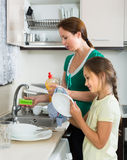 Girl helping mother washing dishes Stock Photos