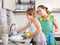 Girl helping mother washing dishes Royalty Free Stock Photography